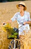 De cyclus van vrouwenpedalen met appelen en bloemen op roggegebied royalty-vrije stock foto