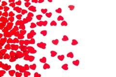De dag decoratieve grens van Valentine ` s van rode die hartenconfettien op witte achtergrond wordt geïsoleerd stock fotografie