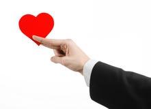 De Dag en de liefde van Valentine als thema hebben: een mens in een zwart kostuum die een rood die hart houden op een witte achte Stock Fotografie