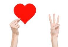 De Dag en de liefde van Valentine als thema hebben: hand die een rood die hart houden op een witte achtergrond wordt geïsoleerd Stock Afbeeldingen