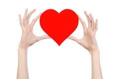 De Dag en de liefde van Valentine als thema hebben: hand die een rood die hart houden op een witte achtergrond wordt geïsoleerd Stock Afbeelding
