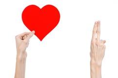 De Dag en de liefde van Valentine als thema hebben: hand die een rood die hart houden op een witte achtergrond wordt geïsoleerd Royalty-vrije Stock Fotografie