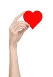 De Dag en de liefde van Valentine als thema hebben: hand die een rood die hart houden op een witte achtergrond wordt geïsoleerd Royalty-vrije Stock Afbeeldingen