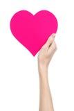 De Dag en de liefde van Valentine als thema hebben: hand die een roze die hart houden op een witte achtergrond wordt geïsoleerd Royalty-vrije Stock Afbeeldingen