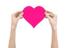 De Dag en de liefde van Valentine als thema hebben: hand die een roze die hart houden op een witte achtergrond wordt geïsoleerd Royalty-vrije Stock Foto