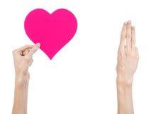 De Dag en de liefde van Valentine als thema hebben: hand die een roze die hart houden op een witte achtergrond wordt geïsoleerd Stock Fotografie