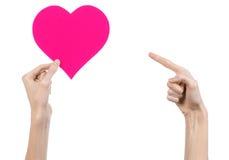 De Dag en de liefde van Valentine als thema hebben: hand die een roze die hart houden op een witte achtergrond wordt geïsoleerd Royalty-vrije Stock Foto's