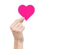 De Dag en de liefde van Valentine als thema hebben: hand die een roze die hart houden op een witte achtergrond wordt geïsoleerd Stock Afbeelding