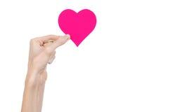 De Dag en de liefde van Valentine als thema hebben: hand die een roze die hart houden op een witte achtergrond wordt geïsoleerd Stock Afbeeldingen