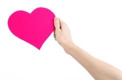 De Dag en de liefde van Valentine als thema hebben: hand die een roze die hart houden op een witte achtergrond wordt geïsoleerd Royalty-vrije Stock Fotografie