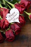 De Dag rode rozen van Valentine op donkere gerecycleerde houten achtergrond - verticaal Stock Foto's