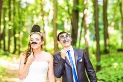De dag van April Fools ' Huwelijkspaar het stellen met stoklippen, masker royalty-vrije stock afbeeldingen