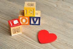 De dag van de valentijnskaart Liefde met kleurrijke alfabetblokken en a wordt gespeld die Stock Afbeelding