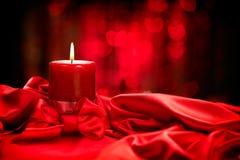 De dag van de valentijnskaart Rode kaars op rode zijde Stock Afbeelding