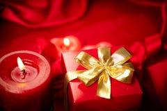 De dag van de valentijnskaart Rode kaarsen en giftdoos Stock Afbeelding