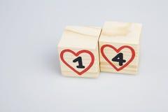 De dag van de valentijnskaart `s Houten kubussen met met de hand geschreven 14de en rode harten Stock Afbeeldingen