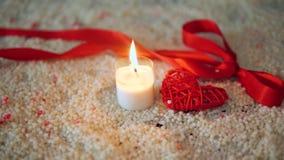De dag van de decoratievalentijnskaart met kaars het branden en lint op zand stock video