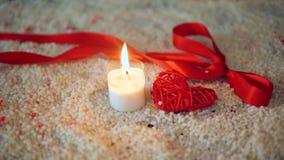 De dag van de decoratievalentijnskaart met kaars het branden en lint op zand stock videobeelden