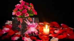De dag van decoratievalentine met giftdozen, kaars het branden en nam bloemblaadjeslengte toe stock footage