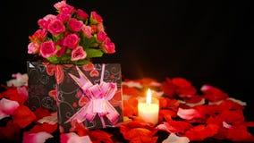 De dag van decoratievalentine met giftdozen, kaars het branden en nam bloemblaadjeslengte toe stock videobeelden