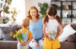 De dag van de gelukkige moeder! De kinderen wenst mamma's geluk en geeft haar een gift en bloemen royalty-vrije stock afbeeldingen