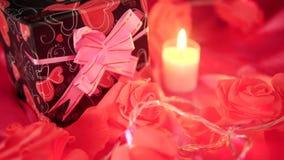De dag van groetvalentine met giftdozen, kaars het branden en bloem nam lengte toe stock videobeelden