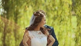 De dag van het huwelijk Bruidegom achter bruid onder de groene bomen Omhels de vlucht in het zonlicht stock footage