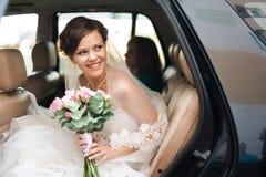 De dag van het huwelijk De bruid zit en glimlacht in een auto met huwelijk Stock Foto