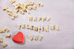De dag van tekstvalentijnskaarten met macaroni in de vorm van brieven en rood hartkoekje wordt geschreven op grijze houten lijsta royalty-vrije stock foto