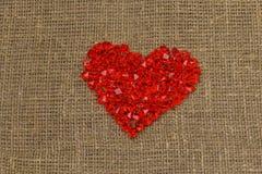 De dag van de valentijnskaart `s Een groot rood plastic glashart van kleine kristallen ligt op een bruine jutezak stock fotografie