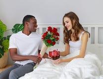 De dag van de valentijnskaart `s gelukkig paar met rode hert en bloemen in bed royalty-vrije stock afbeeldingen