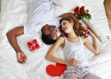 De dag van de valentijnskaart `s gelukkig paar met rode hert en bloemen in bed stock afbeelding