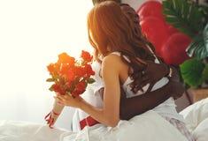 De dag van de valentijnskaart `s gelukkig paar met rode hert en bloemen in bed royalty-vrije stock afbeelding