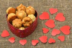 De dag van de valentijnskaart `s De hart-vormige giftdoos is op de zak op de linkerzijde en heeft veel heerlijke cupcakes en veel stock fotografie
