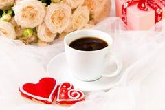 De dag van de valentijnskaart `s Huwelijk Een Kop van koffie en twee peperkoekhart op een achtergrond van rozen Royalty-vrije Stock Foto's