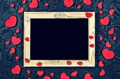 De dag van de valentijnskaart `s Lay-out voor de prentbriefkaar Houten kaderspatie en harten op een zwarte steenachtergrond royalty-vrije stock foto