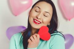 De dag van de valentijnskaart `s Mooie jonge vrouw met hart in haar handen Jonge vrouw met rood hart op witte achtergrond met opb stock afbeelding