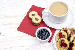 De dag van de valentijnskaart `s ochtendkoffie met gebakjes en harten stock foto's