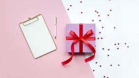 De dag van de valentijnskaart `s Roze giftdoos met rode lintboog Aanwezige vakantie Op witte en roze achtergrond stock foto