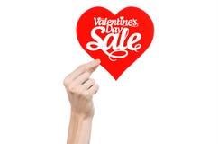 De Dag van Valentine en verkooponderwerp: Hand die een kaart in de vorm van een rood die hart met de woordverkoop houden op witte Stock Fotografie