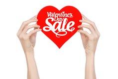 De Dag van Valentine en verkooponderwerp: Hand die een kaart in de vorm van een rood die hart met de woordverkoop houden op witte Stock Foto