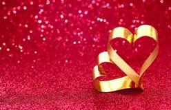 De dag van Valentine ` s schittert achtergrond en twee gouden harten stock fotografie