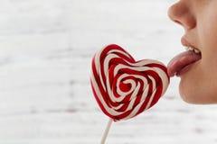 De Dag van Valentine ` s, tong die rood suikergoed in de vorm van een hart, ruimte voor tekst likken stock foto's