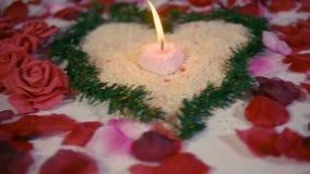 De dag van verrassingsvalentine met decoratiebloem, nam bloemblaadjes en kaars het branden lengte toe stock footage