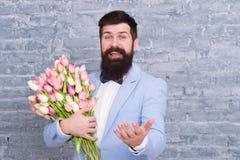 de dag van vrouwen Bloem voor 8 Maart Gebaarde mens met tulpenboeket De lentegift Gebaarde mens met bloemen De datum van de liefd stock foto