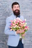 de dag van vrouwen E Internationale vakantie Gebaarde mens met tulpenboeket Bloem voor 8 Maart Het boeket van de de lentegift royalty-vrije stock fotografie