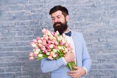 de dag van vrouwen Mooie vrouw in de lente Bloem voor 8 Maart De lentegift Gebaarde mens met bloemen Gebaarde mens met tulpenboek stock afbeeldingen