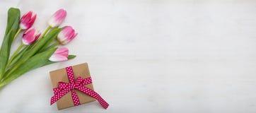 De dag van vrouwen `s Roze tulpen en een gift op witte achtergrond, banner, hoogste mening, copyspace stock foto's