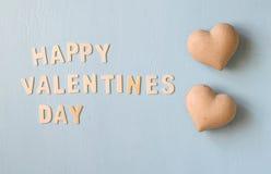 De dag van woorden gelukkige valentijnskaarten maakte met blok houten brieven naast paar van harten op lichtblauwe houten achterg Stock Foto's