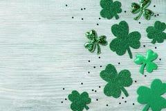De Dagachtergrond van heilige Patricks met groene klaver op witte rustieke raads hoogste mening stock foto